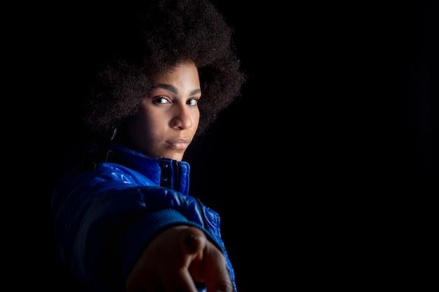 Femme afro mixte posant sur fond sombre vêtements urbains hip hop enregistrement de studio de musique