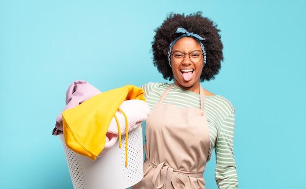 Femme afro noire avec une attitude joyeuse, insouciante et rebelle, plaisantant et tirant la langue, s'amusant. concept de ménage ... concept de ménage