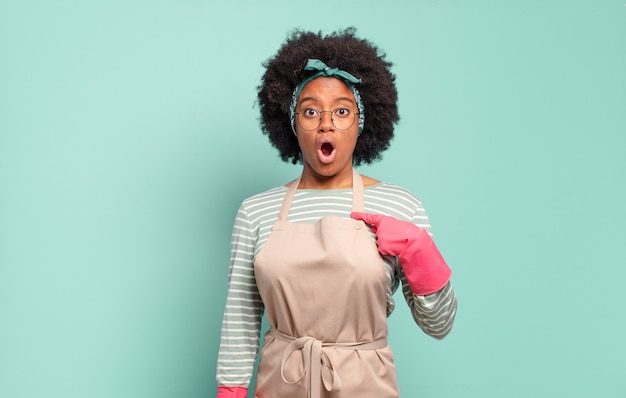 Femme afro noire semblant choquée et surprise avec la bouche grande ouverte, pointant vers soi. concept de ménage.concept de ménage