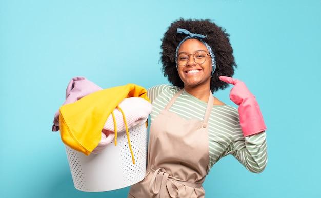 Femme afro noire souriant avec confiance en montrant son large sourire, attitude positive, détendue et satisfaite. concept de ménage ... concept de ménage