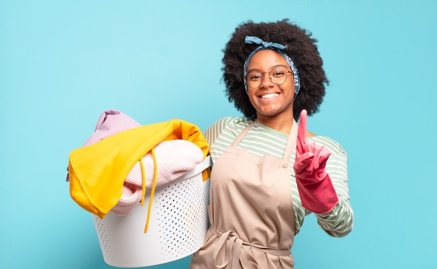 Femme afro noire souriant fièrement et en toute confiance faisant la pose numéro un triomphalement, se sentant comme un leader. concept de ménage ... concept de ménage