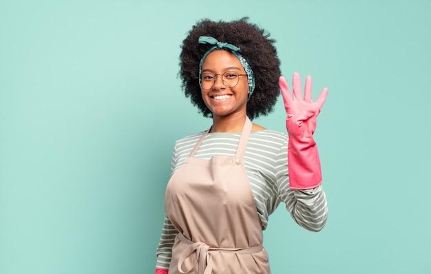 Femme afro noire souriante et à la recherche amicale, montrant le numéro quatre ou quatrième avec la main en avant, compte à rebours.