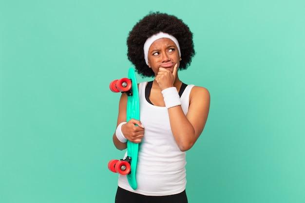 Femme afro pensant, se sentant dubitative et confuse, avec différentes options, se demandant quelle décision prendre. concept de planche à roulettes