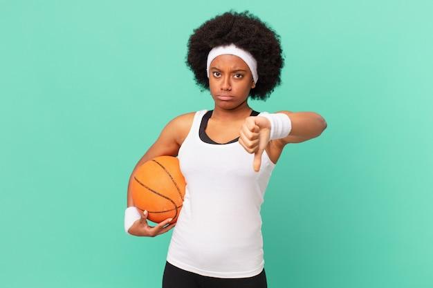 Femme afro se sentant fâchée, en colère, agacée, déçue ou mécontente, montrant les pouces vers le bas avec un regard sérieux. concept de basket-ball