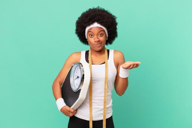Femme afro se sentant perplexe et confuse, doutant, pondérant ou choisissant différentes options avec un concept de régime d'expression drôle