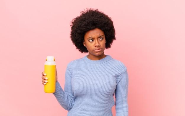 Femme afro se sentant triste, bouleversée ou en colère et regardant de côté avec une attitude négative, fronçant les sourcils en désaccord. concept de smoothie