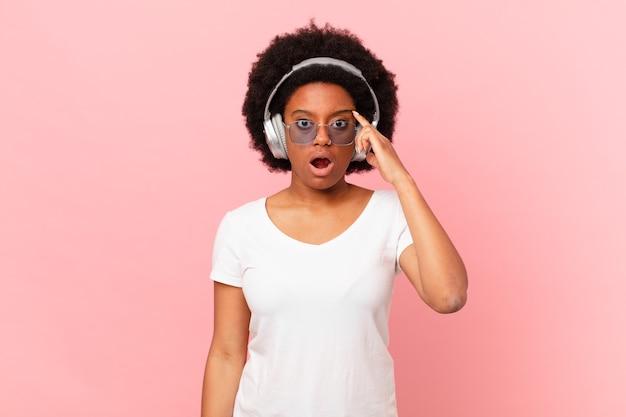 Femme afro semblant surprise, bouche bée, choquée, réalisant une nouvelle pensée, idée ou concept. notion de musique