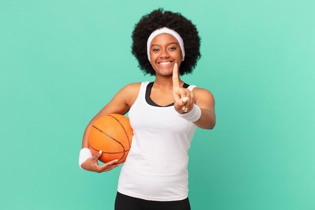 Femme afro souriante fièrement et avec confiance faisant triomphalement la pose numéro un, se sentant comme un leader. concept de basket-ball