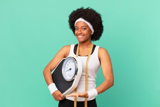 Femme afro souriante joyeusement, se sentant heureuse et montrant un concept dans l'espace de copie avec le concept de régime alimentaire de la paume de la main