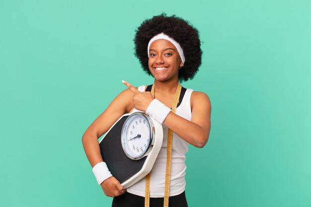 Femme afro souriante joyeusement, se sentant heureuse et pointant vers le côté et vers le haut, montrant l'objet dans le concept de régime de l'espace de copie
