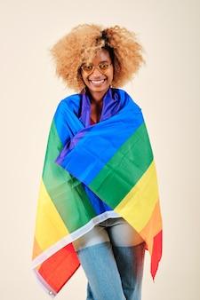 Femme afro souriante recouverte d'un drapeau de fierté lgbt sur fond isolé. concept de communauté et de droits lgbtq.