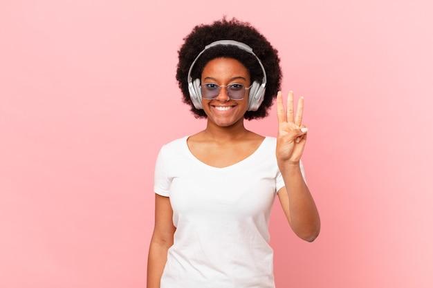 Femme afro souriante et semblant amicale, montrant le numéro trois ou troisième avec la main en avant, compte à rebours. notion de musique