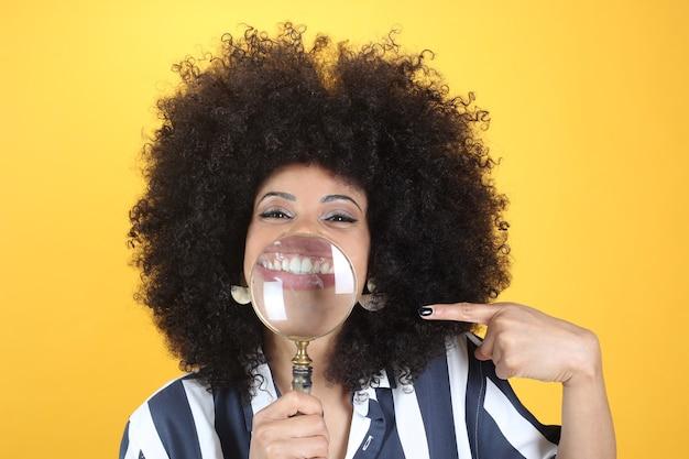 Femme afro avec sourire loupe