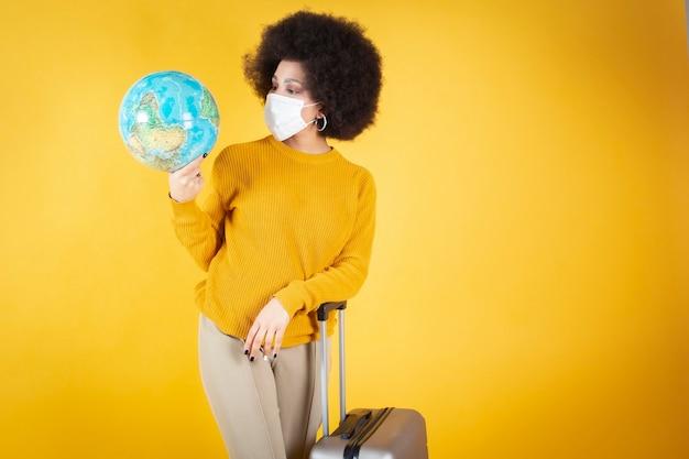 Femme afro avec valise, masque, je ne peux pas voyager, et faire le tour du monde