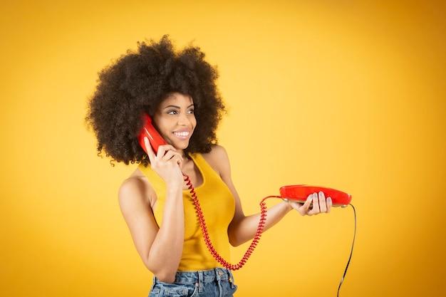 Femme afro avec un vieux téléphone par câble, fond jaune, téléphone rouge femme heureuse satisfaite des vêtements décontractés