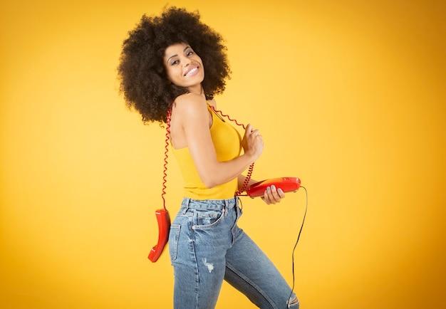 Femme afro avec un vieux téléphone par câble, fond jaune