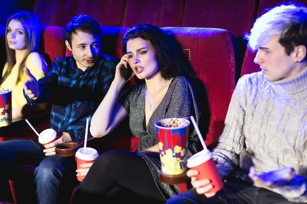 Femme agaçante au téléphone pendant le film au cinéma