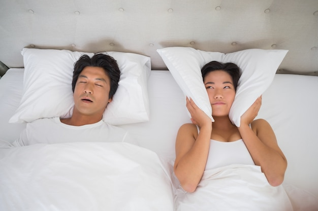 Femme agacée couvrant ses oreilles avec des oreillers pour bloquer le ronflement