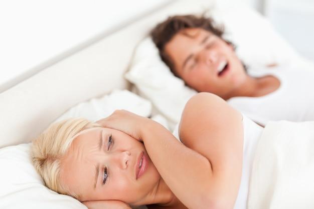 Femme agacée réveillée par ses fiancements ronflant