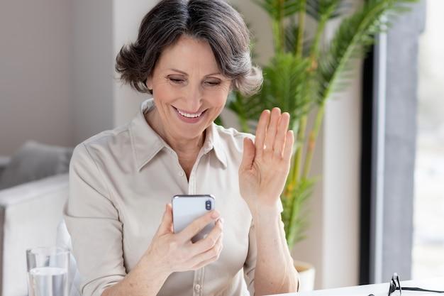 Une femme d'âge caucasien utilise un téléphone portable pour un appel vidéo afin de communiquer en ligne assise au bureau ou à la maison. concept de travail à distance