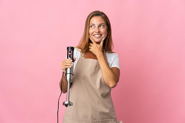 Femme d'âge moyen à l'aide d'un mélangeur à main isolé sur un mur rose en regardant en souriant