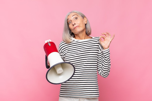 Femme d'âge moyen à l'air arrogante, réussie, positive et fière, se montrant elle-même avec un mégaphone
