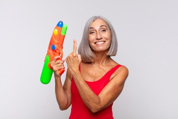 Femme d'âge moyen à l'air excité et surpris pointant vers le côté et vers le haut pour copier l'espace avec un pistolet à eau