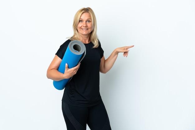 Femme d'âge moyen allant à des cours de yoga tout en tenant un tapis isolé sur blanc surpris et pointant le doigt sur le côté
