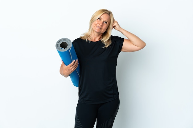 Femme d'âge moyen allant à des cours de yoga tout en tenant un tapis isolé sur un mur blanc ayant des doutes et avec l'expression du visage confus