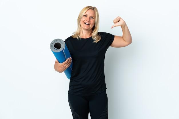 Femme d'âge moyen allant à des cours de yoga tout en tenant un tapis isolé sur un mur blanc fier et satisfait de soi