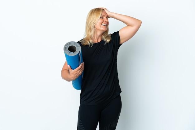 Femme d'âge moyen allant à des cours de yoga tout en tenant un tapis isolé sur un mur blanc a réalisé quelque chose et l'intention de la solution