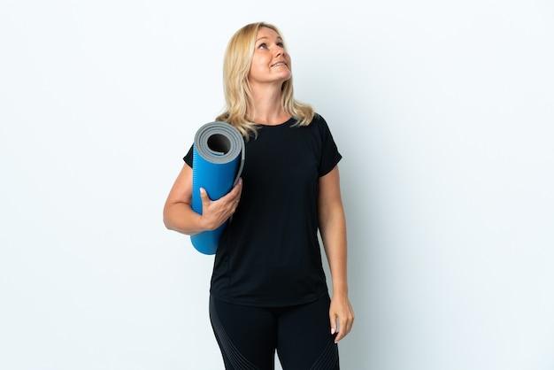 Femme d'âge moyen allant à des cours de yoga tout en tenant un tapis isolé sur un mur blanc en regardant en souriant