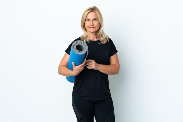 Femme d'âge moyen allant à des cours de yoga tout en tenant un tapis isolé sur un mur blanc en souriant beaucoup