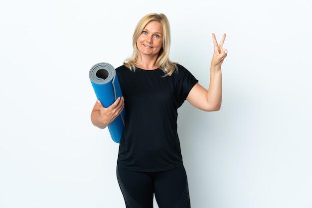 Femme d'âge moyen allant à des cours de yoga tout en tenant un tapis isolé sur un mur blanc souriant et montrant le signe de la victoire