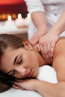 Une femme d'âge moyen allongée sur une table de massage dans un salon de beauté avec des pierres chaudes sur le dos.