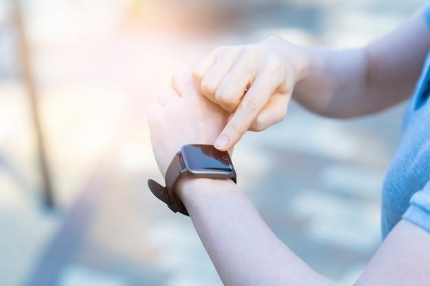 Femme d'âge moyen asiatique d'exploitation d'une smartwatch à l'extérieur
