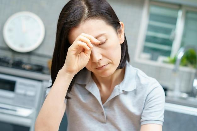 Femme d'âge moyen asiatique souffrant de maux de tête dans la chambre