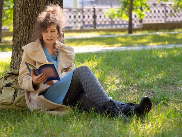 Femme d'âge moyen assise sur l'herbe et lisant le concept de livre d'un repos des smartphones gadgets et ...