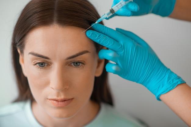 Une femme d'âge moyen aux cheveux noirs ayant une procédure d'injections beaty