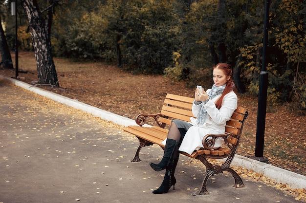 Femme d'âge moyen aux cheveux roux avec un smartphone à la main est assise sur un banc dans le parc et communique sur les réseaux sociaux.