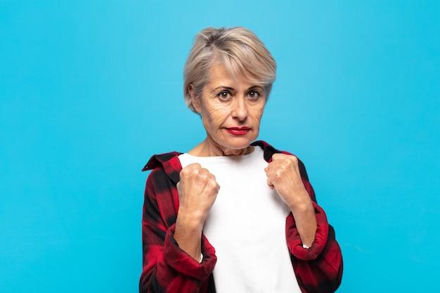 Femme d'âge moyen ayant l'air confiante, en colère, forte et agressive, les poings prêts à se battre en position de boxe