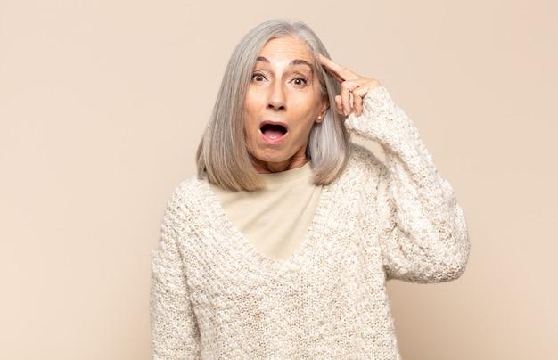 Femme d'âge moyen ayant l'air heureuse, étonnée et surprise, souriante et réalisant de bonnes nouvelles incroyables et incroyables