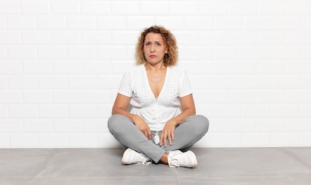 Femme d'âge moyen ayant l'air inquiète, stressée, anxieuse et effrayée, paniquant et serrant les dents