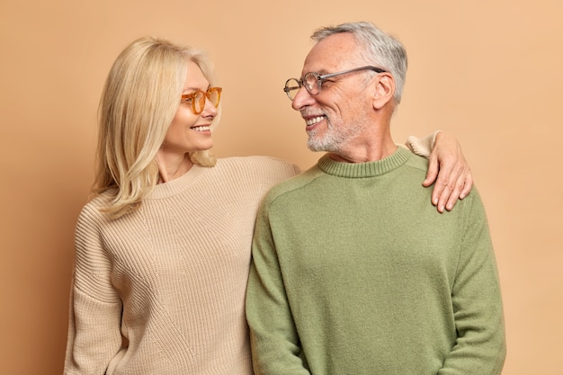 Femme d'âge moyen bienveillante embrasse son mari regarde avec amour et large sourire
