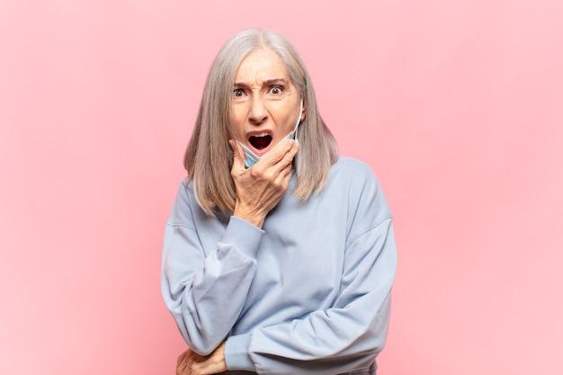 Femme d'âge moyen avec la bouche et les yeux grands ouverts et la main sur le menton, se sentant désagréablement choquée, disant quoi ou wow