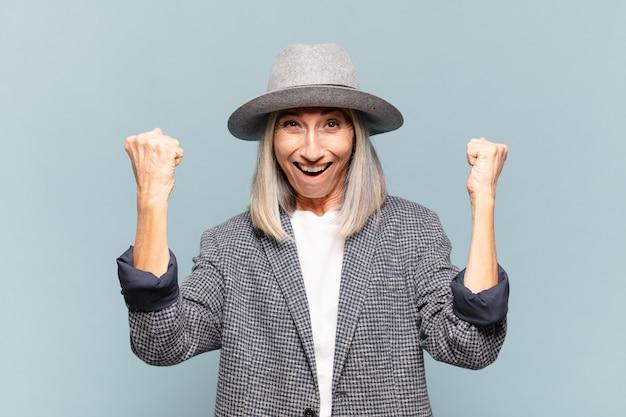 Femme d'âge moyen célébrant un succès incroyable comme une gagnante, l'air excitée et heureuse en disant: prenez ça!