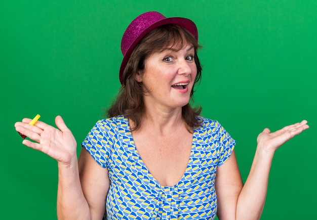 Femme d'âge moyen en chapeau de fête heureux et excité tenant un sifflet célébrant la fête d'anniversaire debout sur un mur vert
