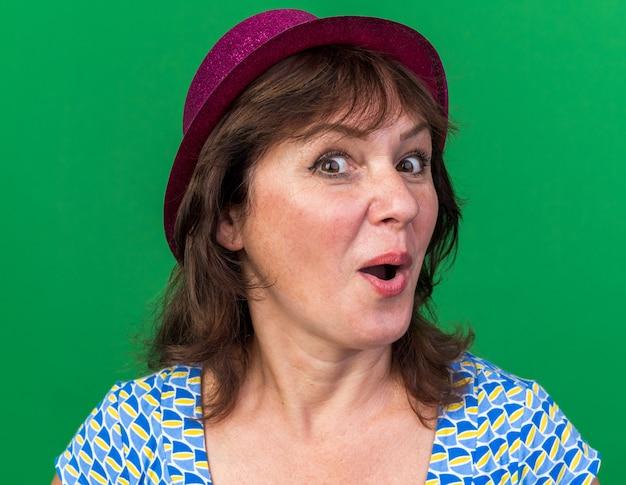 Femme d'âge moyen en chapeau de fête heureux et surpris de célébrer la fête d'anniversaire debout sur un mur vert