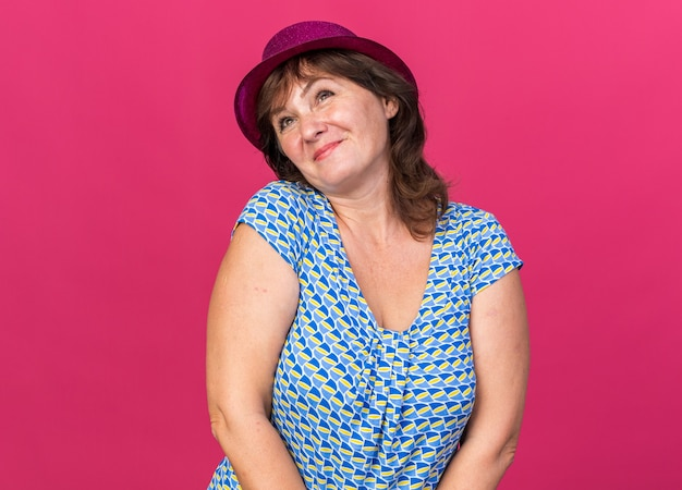 Femme d'âge moyen en chapeau de fête levant le sourire heureux et joyeux célébrant la fête d'anniversaire debout sur le mur rose