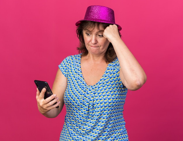 Femme d'âge moyen en chapeau de fête regardant l'écran de son smartphone étant confuse célébrant la fête d'anniversaire debout sur un mur rose